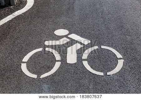 Close up the sign of bicycle route marked on the asphalt street background.