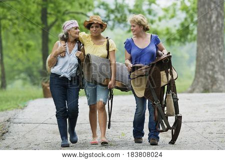 Multi-generation Hispanic women carrying horse saddle and equipment