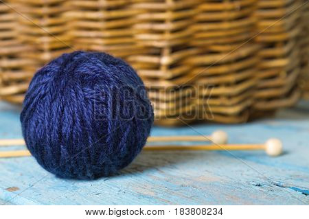 Hank of blue wool and knitting spokes on an old wooden table