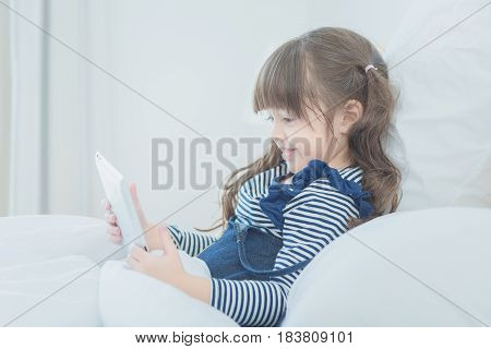 Cute Little Girl Enjoy Watching Cartoon On Smart Tablet With Cute Doll While Sitting On Bed In Kid's