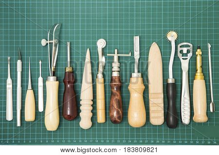 Leather craft tools on green rubber background