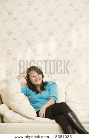 Chinese woman relaxing on sofa