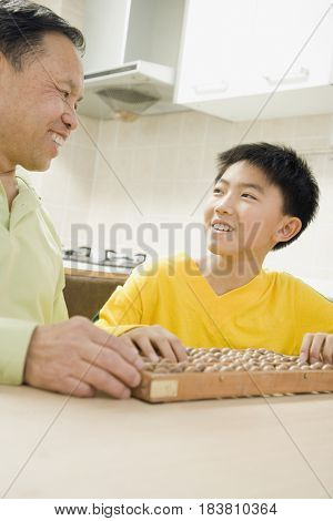 Chinese grandfather teaching abacus to grandson