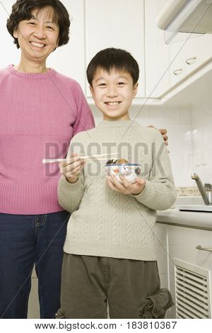 Chinese grandmother and boy with bowl of food