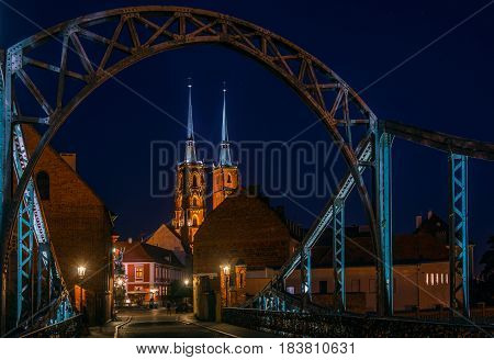 Night scene in Wroclaw. Illuminated old buildings and cathedral. Arch of bridge in foreground.