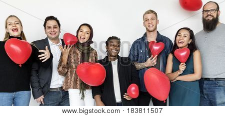 Group of diversity people party fun with heart balloon