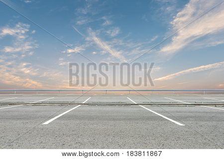 Empty parking lot on sunset sky background