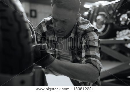 Do it right. Accomplished gifted precise man fixing some problems while repairing a bike and fulfilling his job in repair shop