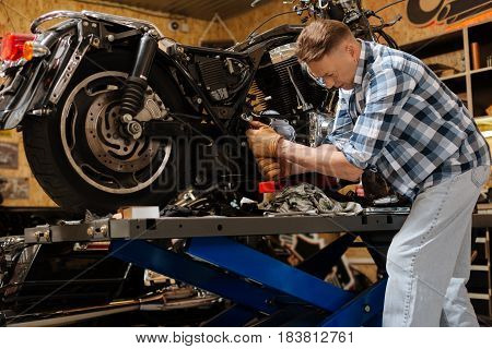 Make it sit tighter. Reliable certified competent mechanic fixing some bolts on classy heavy bike while running a checkup and solving some problems