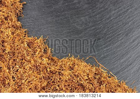 Dried shredded hand rolling smoking tobacco on a stone slate background