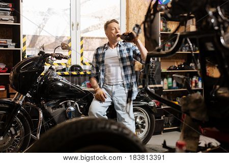 Cheers to craftsmen. Diligent trained virile guy finishing his workday in the repair shop by relaxing on a motorbike he currently repairing