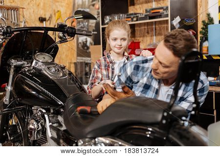 Curious little child. Charming skilled top mechanic asking for daughters help while working on his vehicle and spending time together in workshop