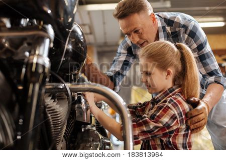Try a little harder. Lovely positive intelligent family spending time together and fixing the bike while the dad explaining something to his daughter