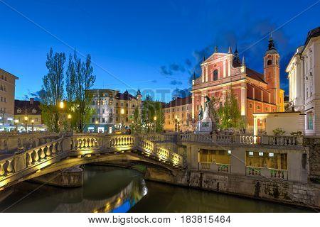 Romantic Ljubljana's city center at dusk: river Ljubljanica, Triple Bridge - Tromostovje, Preseren square and Franciscan Church of the Annunciation. Ljubljana, Slovenia, Europe.