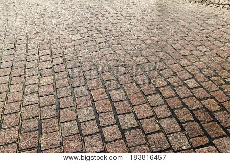 Stone pavement in perspective. Stone pavement texture. Granite cobblestoned pavement background. Abstract background of old cobblestone pavement close-up.