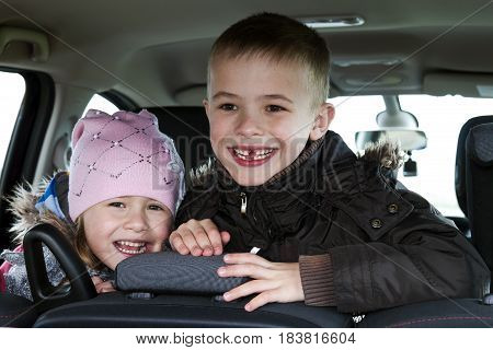 Two pretty little children boy and girl in a car interior