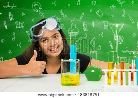 indian schoolgirl posing with science equipments like test tube, flash, beaker etc in the chemistry lab, smiling and looking at camera with green chalkboard background with science doodles