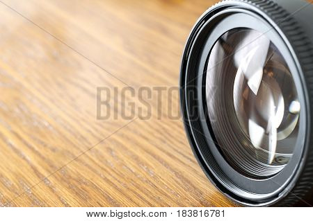 Professional Photography Equipment Photographer Work Kit. Close-up macro shot of photo camera objective lens on wooden table. Shallow DOF