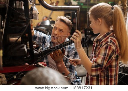 Here is the issue. Decent hardworking accomplished expert asking his child giving him a wrench for tightening up the bolt on a bike