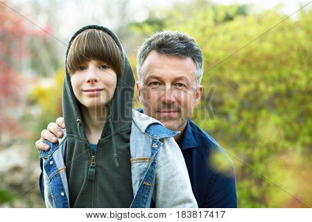 Father with son outdoors portrait. Mid adult father and his 11 years son posing over spring outdoor.
