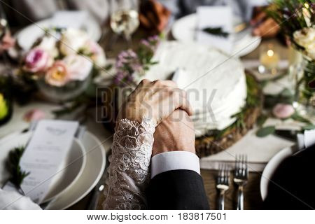 Bride and Groom Holding Hands Each Other on Wedding Reception