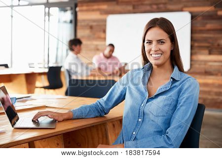 Young dark haired woman sitting in office looking to camera