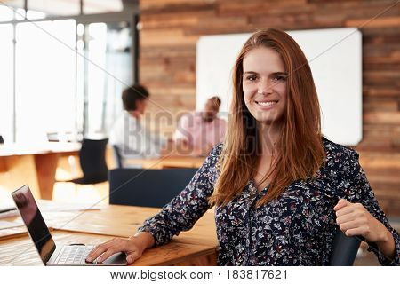 Young white woman with long red hair sitting in office