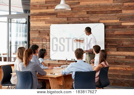 Young black man at whiteboard giving a business presentation