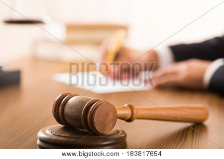 Closeup of Gavel with Lawyer Writing on Background