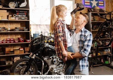Precious moments. Amusing creative active child wanting wearing fathers hat and taking it off while he holding her in his arms