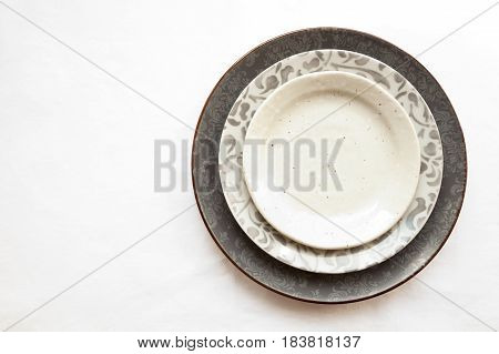 Stack of empty ceramic plates isolated on white background with copy space. Stylish gray dishes decorated with floral pattern. Beautiful vintage crockery top view