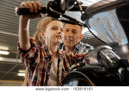 Adorable kid. Excited charismatic vibrant lady spending time at dads workshop and sitting on a bike while imagining taking a road trip on it