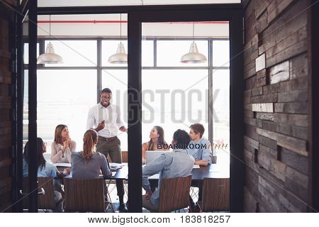 Man stands addressing colleagues at a meeting in a boardroom