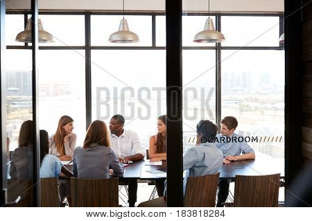 Team in a business boardroom meeting seen through glass wall
