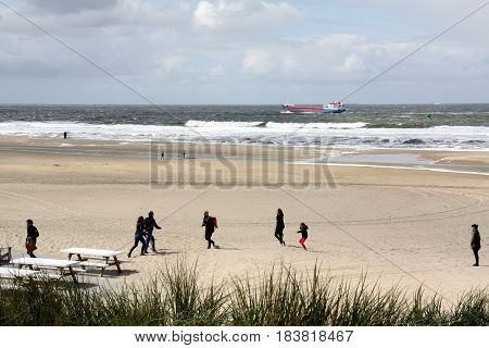 Vlieland. May-15-2016. People walking on the beach of the island Vlieland. On the background a freighter in the North Sea. The Netherlands