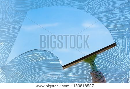 Human hand cleaning window from outside over sky background
