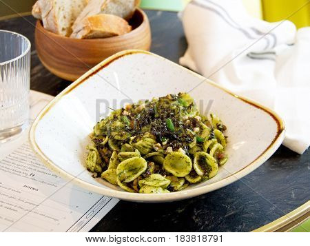 Pasta orecchiette con pesto, olivas y frutos secos Orecchiette pasta with pesto, olives and nuts