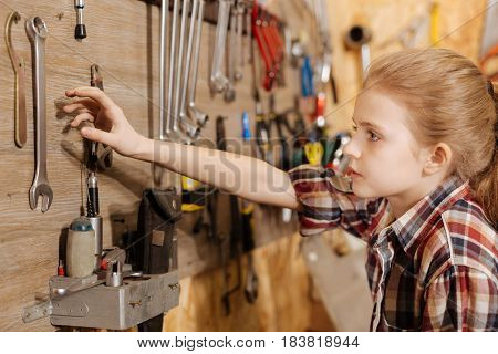 Is it heavy. Passionate energetic determined girl spending time at fathers garage and examining things while reaching for a wrench on the wall