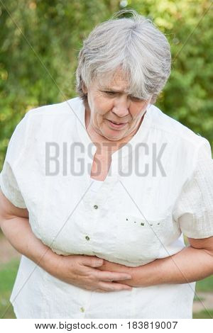 Senior woman suffers from stomachache