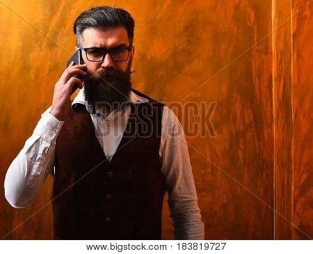 Bearded man long beard. Brutal caucasian unshaven serious hipster with glasses and moustache talking by cell phone wearing white shirt suede waistcoat on brown studio background
