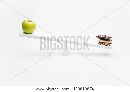 Close-up View Of Apple And Chocolate Balancing On Seesaw, Healthy Living Concept