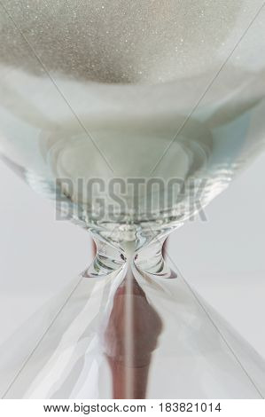 Close up white sand flowing of vintage wooden hourglass on white background time concept.