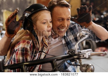 Hilarious couple. Positive artistic cute dad and daughter making funny faces and looking at their reflection while sitting on a bike in garage