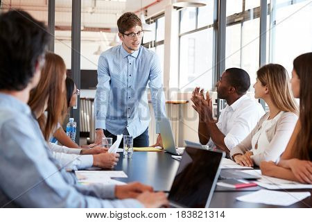 Young man stands addressing colleagues at business meeting