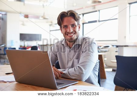 Young man in office using laptop computer smiling to camera