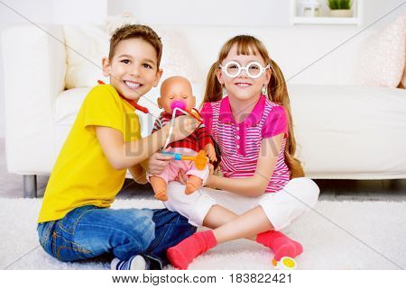 Funny happy brother and sister playing together in doctors. Family at home. Pediatry.