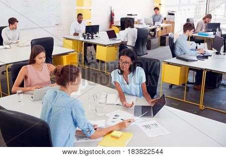 Three women working together in a busy office, elevated view