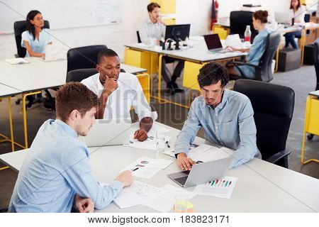 Young male business team brainstorming in busy office