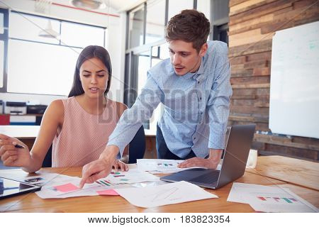 Young man stands working with a woman at her desk in office