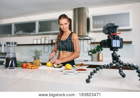 Young Female Blogger Recording Content For Videoblog In Kitchen.